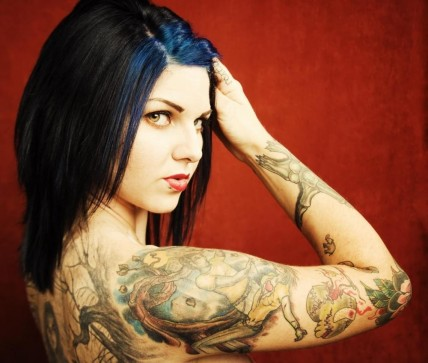 Woman With Tattoos On Her Arm And Back With Tattoos
